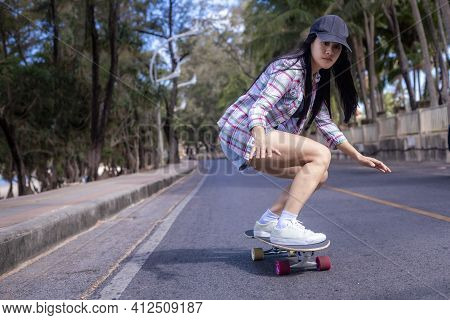Young Asian Women Play Surf Skate Board At Beach Road Outdoors On Morning. Happy Women Play Surfskat