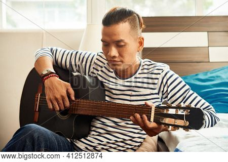 Serious Young Vietnamese Man Spending Time In Dorm, Playing Guitar And Singing