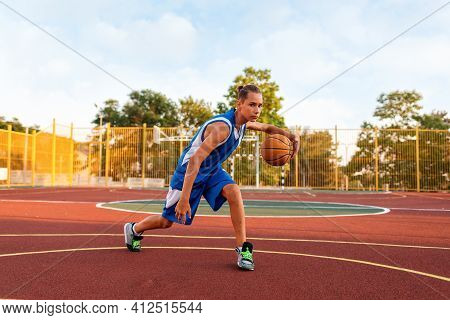 Basketball. A Teenage Boy In Blue Sportswear Plays A Basketball. In The Background Is A Sports Field