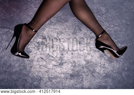 Woman Legs In Black Fetish Shiny Patent Leather Stiletto High Heels With Ankle Strap Near Wall Of Ve