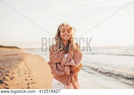 Headshot Of Beautiful Blonde Slim Woman Wearing White Dress And Pastel Cardigan On Beach Of Sea Or O