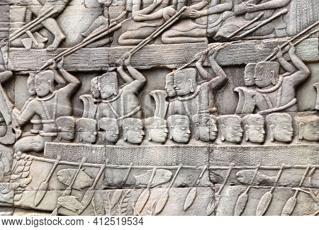 Bas-relief on stone wall of Prasat Bayon temple. Carvings scene with people in boats,  Angkor Wat (Angkor Thom), Siem reap, Cambodia, Indochina. UNESCO world heritage Site