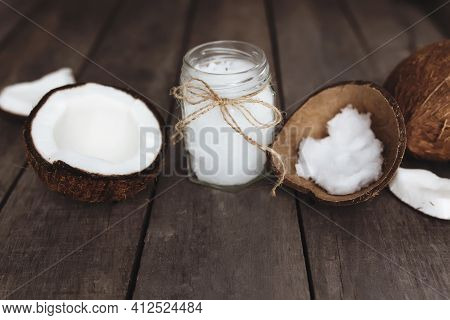 Broken Coconuts On Gray Wooden Background With Jar Of Raw Organic Extra Virgin Coconut Oil. White Co