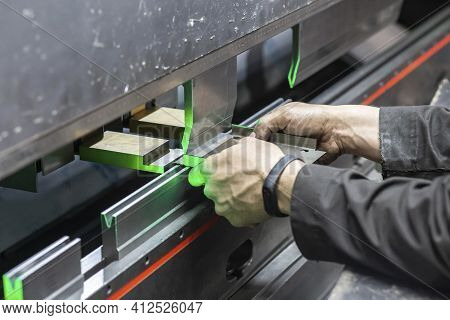 Worker Holds A Part In A Cnc Bending Machine