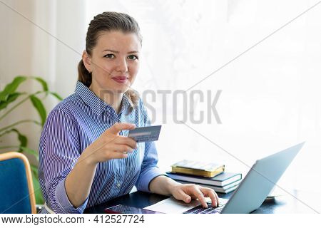 Smiling Girl With Bank Credit Card Useing Laptop At Home. Young Happy Woman Make Online Purchase, Pa