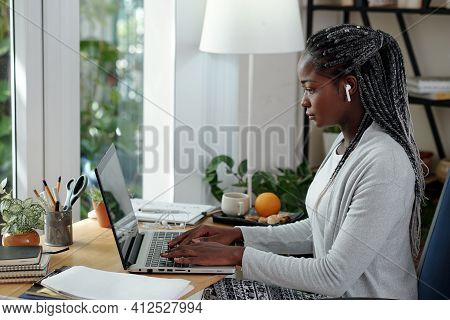 Serious Young Black Woman With Dreadlocks Working On Laptop At Her Desk At Home And Writing Essay Fo