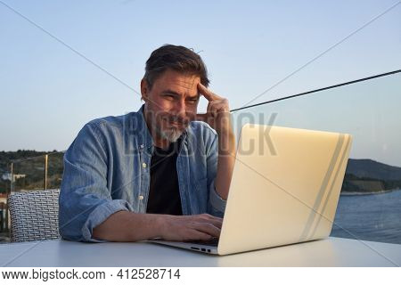 Happy man working online with laptop computer on terrace. Home office, browsing internet, tele working, video chat. Businessman on vacation at sea. Escape, freedom, getaway.
