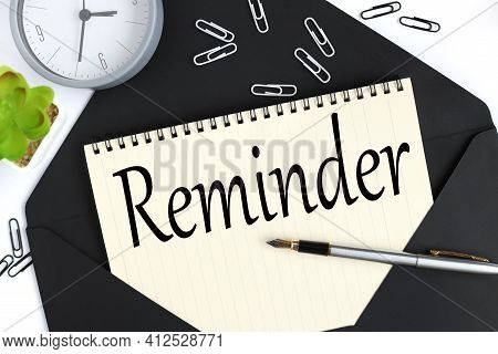 Reminder. Text On A Sheet Of Notepad On A Black Envelope On A Light Background