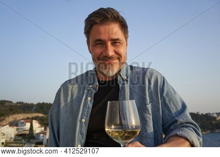 Happy man drinking wine outdoor holding wine glass, smiling. Wine tasting in sunset. Portrait of mature age, middle age, mid adult man in 50s.