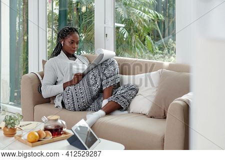 Concentrated Black Young Woman In Loungewear Working From Home, She Is Sitting On Sofa And Reading B
