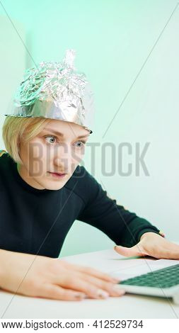 Vertical. Fearful Young Woman With Aluminum Hat Browsing Social Media. Conspiracy Theory About 5g Mi