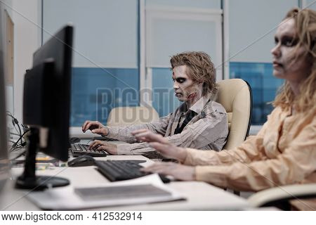 Zombie businessman sitting in front of monitor with dead female colleague working next to him