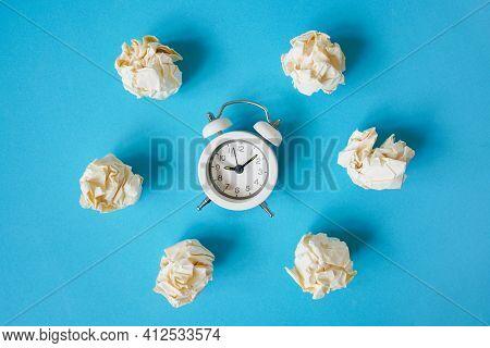 Crumpled Paper Balls Around White Alarm Clock On Grunge Blue Paper Background For Business , Deadlin
