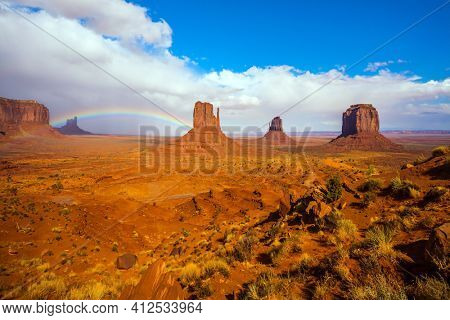Picturesque rainbow across the sky. Monument Valley is unique geological formation. Huge masses of red sandstone - outliers on the Navajo Indian Reservation. The USA