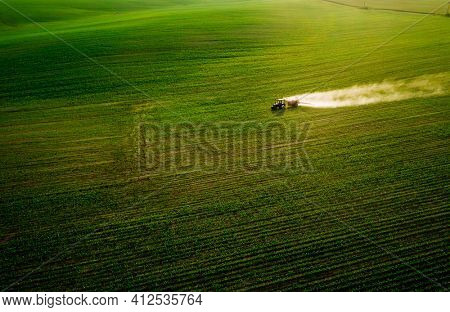 Scenic top view of a tractor spraying green fields. Organic irrigation field. Location place of Ukraine agrarian region, Europe. Aerial photography, drone shot. Industry of agronomy. Beauty of earth.