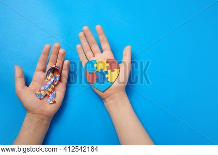 Adult And Autistic Boy Hands Holding Puzzle Heart Shape And Ribbon. Autism Spectrum Disorder Family