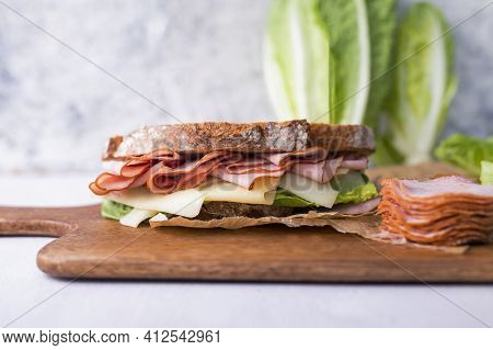 A Sandwich Made Of Crispy Bread, Dried, Smoked Sausage, Cheddar, Lettuce And A Pile Of Sliced Homema