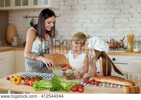 Family Prepares Lunch In The Kitchen. Mom Teaches Her Daughter And Son To Prepare A Salad Of Fresh V