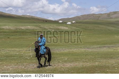 Baruuntunuun, Mongolia - August 8, 2019: Steppe With Yurts And Shepherd On Horseback, Hills And Moun