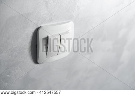 Light Switch, A Plastic Mechanical Switch Of White Color Installed On A Light Gray Wall.