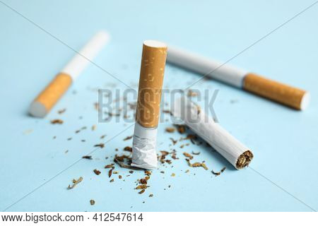 Broken And Whole Cigarettes On Light Blue Background, Closeup. Quitting Smoking Concept