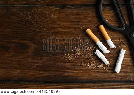 Cut Cigarettes And Scissors On Wooden Table, Flat Lay With Space For Text. Quitting Smoking Concept