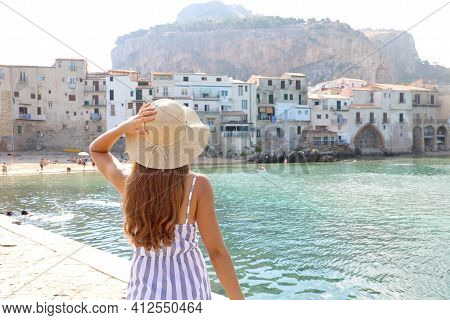 Summer Holiday In Italy. Back View Of Young Woman With Straw Hat And Striped Dress With Cefalu Villa