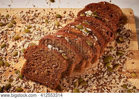 Sliced Whole-grain Bread, Sprinkled With Grains On A Wooden Board. Close-up, Macro