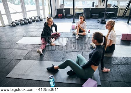 Athletic Young Ladies Discussing Workout Plan On Gym Floor
