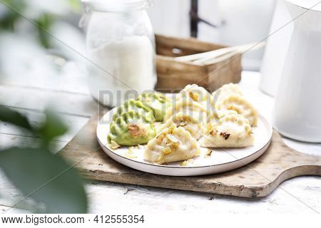 Traditional Pierogi And Green Pierogies With Spinach With Chopped Fried Onion On A White Plate. Rust