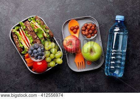 Healthy school lunch box with sandwich and fresh vegetables, water bottle, nuts and fruits. Top view flat lay