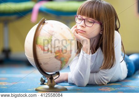 Bored Pre-teen Girl Wearing Glasses Looking At A Globe Lying On The Floor.
