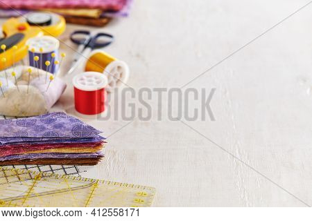 Ruler, Cutting Mat, Stack Of Multi-colored Pieces Of Fabric, Pincushion, Spools Of Thread, Scissors,