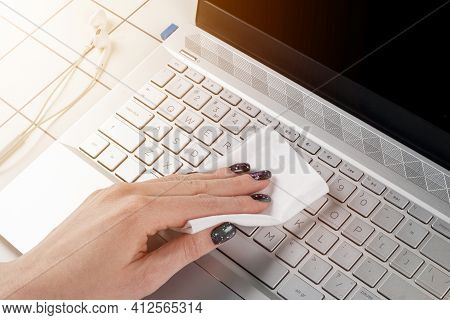 Woman Cleaning Computer Keyboard. Female Hands Disinfecting Laptop Keyboard With Antivirus Wet Wipes