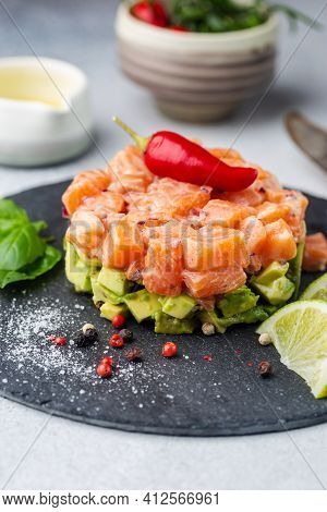Delicious Avocado And Raw Salmon Salad, Tartare, Served On A Black Plate With Lime, Light Background