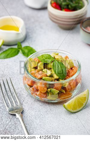 Delicious Avocado And Raw Salmon Salad, Tartare, Served Glass Jar With Lime, Light Background