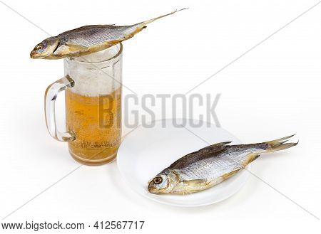Two Salted And Air-dried Roach Fish Lie On A Beer Glass With Lager Beer And On Dish On A White Backg