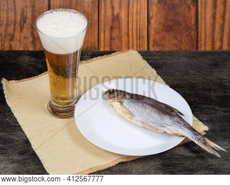 Salted And Air-dried Roach Fish On Dish And Beer Glass With Lager Beer On A Napkin On A Dark Table