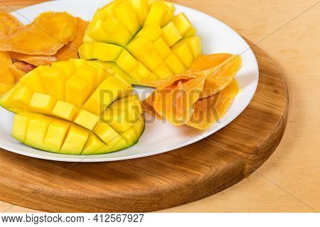 Dried Slices Of Mango Pulp And Cut Fresh Mango Halves On White Dish On A Wooden Serving Board, Fragm