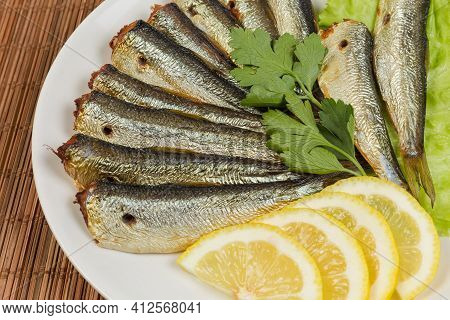Smoked Headless Sprats And Lemon Slices With Greens On Dish On A Bamboo Table Mat, Fragment Close-up