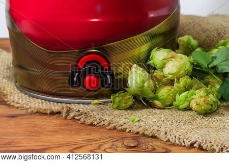 Bottom Part Of The Red Disposable Mini Keg Of Beer With A Built-in Beer Tap Among The Hop Cones On S