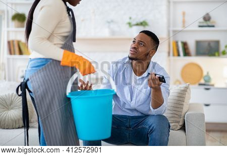 Lazy Black Man Watching Tv While His Wife Doing Home Cleanup, Having Fight With Her, Not Wanting To