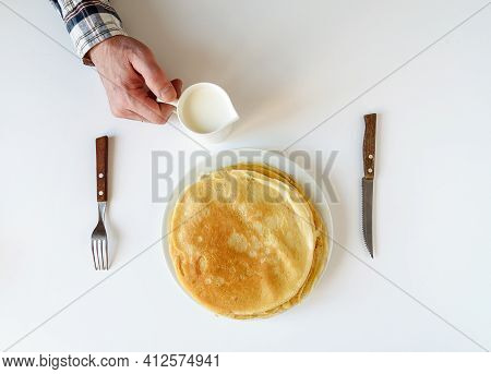 Men\'s Hands With A Knife And Fork. There Are A Lot Of Pancakes On A White Plate. Thin Pancakes With