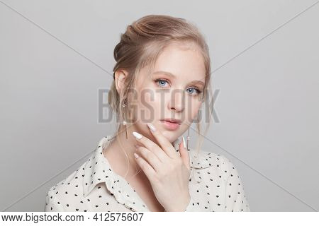 Portrait Of Young Gentle Woman With Updo Hairdo On White Background