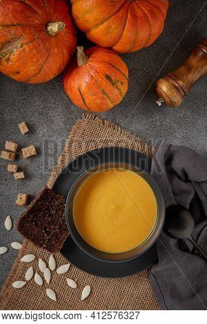 Pumpkin cream soup. Lenten menu. Healthy, vegetarian food. Bowl with soup  and orange pumpkins on gray background. Top view.