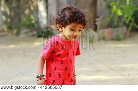 A Little Boy Of Indian Origin Looking At The Ground With Astonishment, India.concept For Childhood J