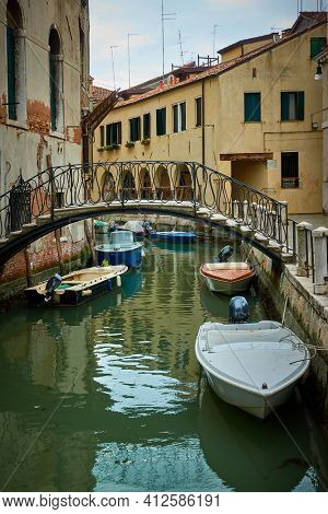 Venetian canal with bridge and moored motorboats, Venice, Italy.