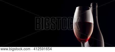 A Glass And A Bottle Of Red Wine On A Black Background. Panoramic Photo, Copy Space