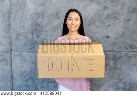 Kind Smiling Asian Female Volunteer With Straight Dark Hair Holding A Cardboard Box, Looking Directl