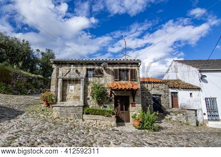 Belmonte, Portugal; May 2017 : Deserted Alley And Charming Old Small House With Stone Niche For Sain